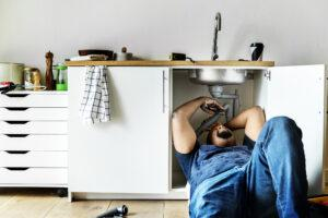 Plumber man fixing kitchen sink Compare Boiler Quotes